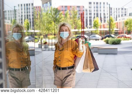 Young Happy Woman Shopaholic In Protective Mask On Face With Paper Bags In Hands. Beautiful Girl In