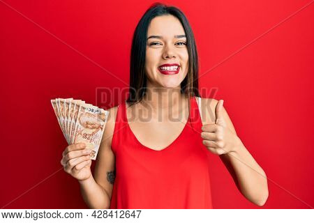 Young hispanic girl holding 50 turkish lira banknotes smiling happy and positive, thumb up doing excellent and approval sign