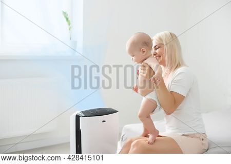 Mother And Baby Near Air Purifier At Home.