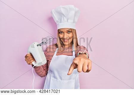 Beautiful hispanic woman holding pastry blender electric mixer pointing to you and the camera with fingers, smiling positive and cheerful