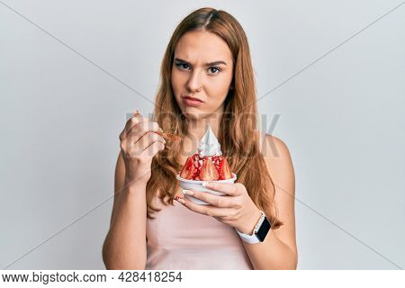 Young blonde woman eating strawberry ice cream skeptic and nervous, frowning upset because of problem. negative person.