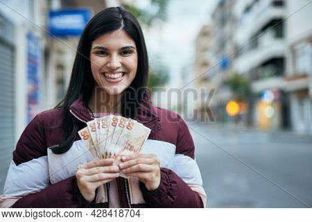 Young hispanic girl smiling happy holding turkish lira banknotes at the city.