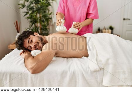 Young hispanic man smiling happy reciving herbal pouches thai massage at beauty center.
