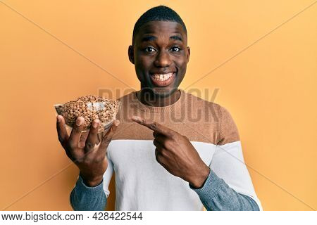 Young african american man holding bowl with lentils smiling happy pointing with hand and finger