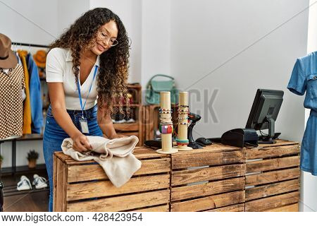Young latin shopkeeper woman smiling happy folding sweater at clothing store.