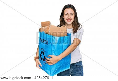 Young beautiful woman holding recycling wastebasket with paper and cardboard looking positive and happy standing and smiling with a confident smile showing teeth