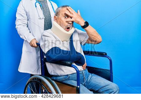 Handsome senior man with beard sitting on wheelchair with neck collar peeking in shock covering face and eyes with hand, looking through fingers with embarrassed expression.