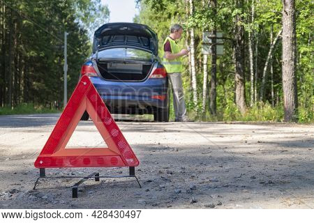 Close-up Of A Portable Reflective Red Warning Triangular Sign On The Side Of A Rural Road Near A Car