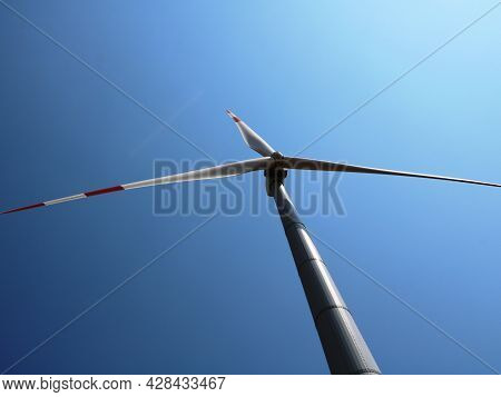 A Propeller Of A Wind Turbine With Three Blades Against A Blue Sunny Sky, The Use Of Energy Innovati