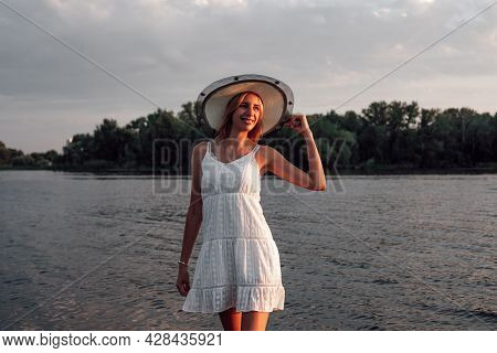 Photo Of A Woman In A Straw Hat. A Beautiful Happy Young Blonde In A White Summer Lace Dress And A S