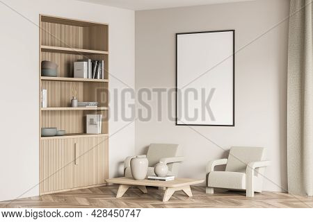 Empty Framed White Banner Near The Corner Of The Beige Living Room With Niche Bookshelf. Two Armchai