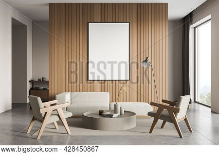 Banner On Wooden Wall In The Living Room Space, Having Sofa, Two Armchairs, Round Coffee Table Witho