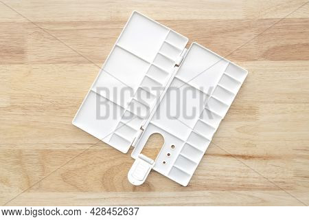 Empty Watercolor Palette Background. White Plastic Paint Palette. Watercolor Tray On Wood.
