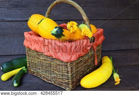 Fresh Zucchini In A Basket. Zucchini With Flowers On The Old Wooden Table