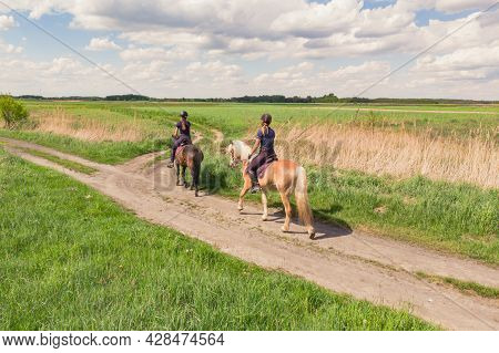 Two Horse Riders On A Flaxen Horse With A Shiny Horse Coat And A Dark Bay Horse Moving Across The Be