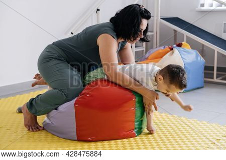 Therapist Doing Exercises On The Mat With Disabled Child. Boy With Cerebral Palsy Having Rehabilitat