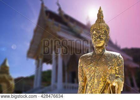 Golden Buddha Standing In Front Of Buddhist Church In Thailand.