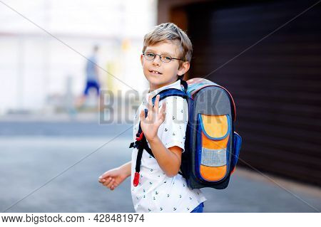 Happy Little Kid Boy With Glasses And Backpack Or Satchel. Schoolkid On The Way To School. Portrait