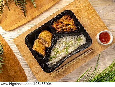 Flat Lay Of Rice With Pork Roll And Chicken Stew Served With Sweet Chili Sauce On Bamboo Chopping Bo