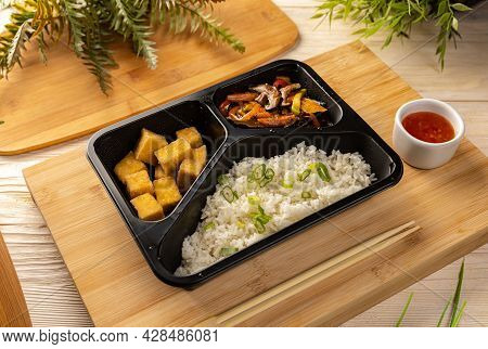 Rice With Tofu And Vegetable Stew In Take-out Box On Bamboo Chopping Board