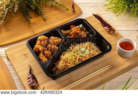 Noodles With Chicken Stew And Breaded Chicken Cubes In Take-out Box On Bamboo Chopping Board