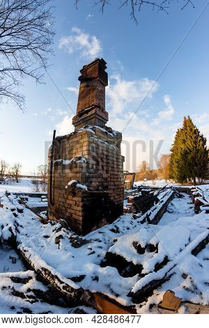 Remains Of A Burned Down House With A Brick Oven In The Middle Of A Snowy Nature, A Chimney On The A