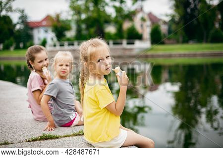 Siblings Enjoying Ice Cream Together. Three Little Girls Eats Ice Cream Outdoors Near The Pond