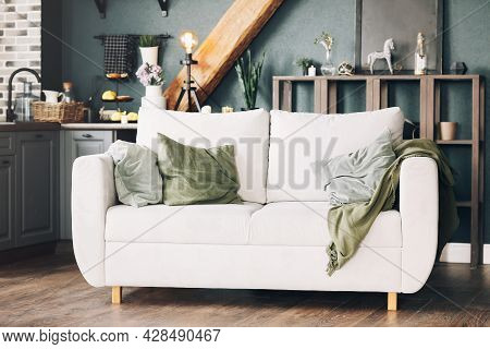 White Sofa With Green And Grey Velour Cushions Standing In American Style Modern Kitchen Interior, W