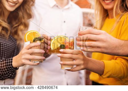 Anonymous Men And Women Clinking Glasses Of Fruit Cocktails And Proposing Toast During Party