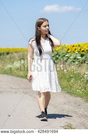 A Young Girl Of 17-20 Years Old Is Walking In A White Dress Along The Road Along A Field With A Bloo