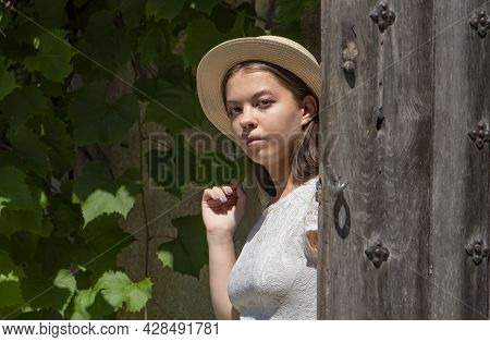 A Young Girl 17-20 Years Old In A White Dress Straw Hat Opens A Wooden Door And Leaves The House 1.