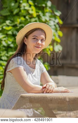 A Young Girl Of 17-20 Years Old In A Straw Hat And A White Dress, Sitting At A Wooden Table Against
