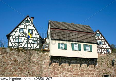 Old House Built Over Medieval City Wall Next To Two Half-timbered Houses In Hirschhorn In Southern G