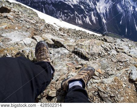 Man Feet On Rock Rocks In Mountain Trekking Boots Over A Cliff In The Snowy Mountains. The Concept O