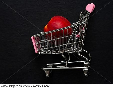 One Red Yellow Nectarine Is Lying In A Small Shopping Trolley. Exotic Tropical Fruits In A Toy Metal