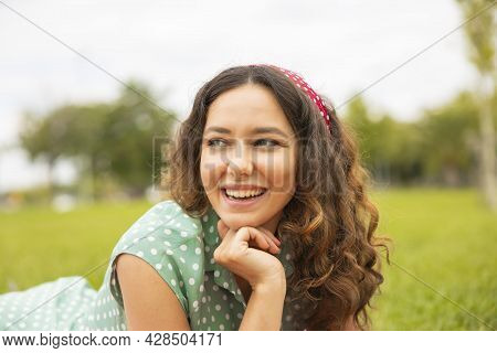 Portrait Of Young Brunette Woman Having Fun In The Park
