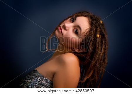 Portrait Of  Young Woman With Dreadlocks Against A Dark Background