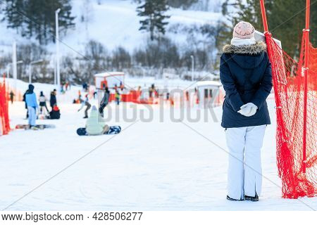 A Woman Put Her Hands Behind Her Back Looking At The Slope Of The Ski Slope, On Which Her Children R