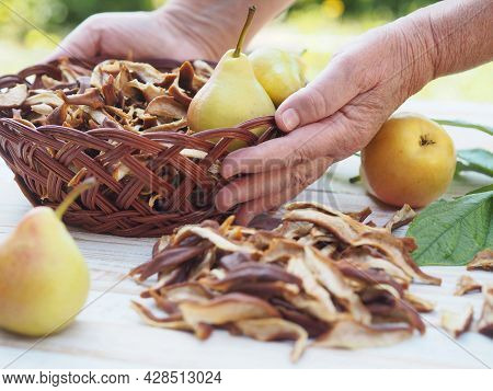 The Season For Harvesting Dried Fruits For Future Use. Woman's Hands Hold Dried Pears. Natural Backg