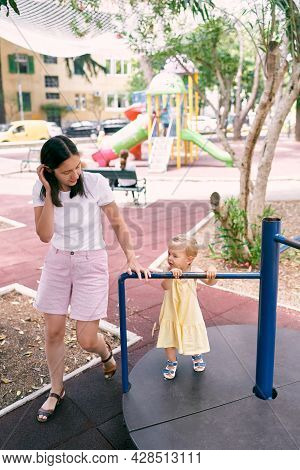 Mom Circles The Little Girl On A Turntable Swing