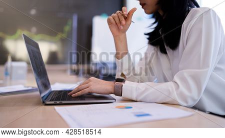 An Office Lady Or Bank Officer Is Working Hard On The Laptop Computer On Company Statistics, Income,