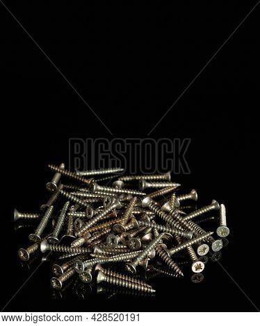 Bunch Of Small Screws Close Up. Metal Screws, Iron Screws. Self-tapping Screws On Black Background.
