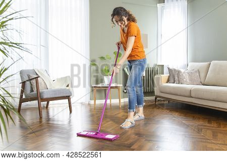 Young Housewife Cleaning Wooden Parquet Using Microfiber Mop Pad. Routine House Chores Concept