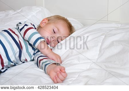 Sleeping Child In Bed. Cute Little Kid Sleeps Sweetly On Cozy White Blanket On Its Side. 2 Years Old