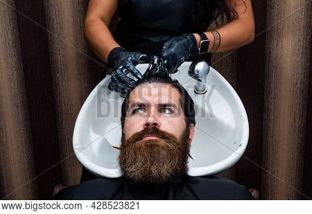 Brutal Hipster With Moustache Wash Hair Before New Hairstyle. Barbershop Washbasin. Male Trendy Hair