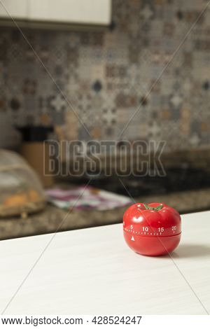 Red Tomato-shaped Kitchen Timer With Cooking In The Background. Brazilian Cuisine. Kitchen Concept.