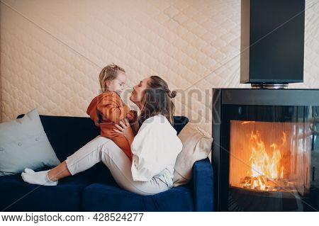 Mother And Child Sitting And Playing On Sofa Near Fireplace. Single Parenting. Mom And Baby Child. P