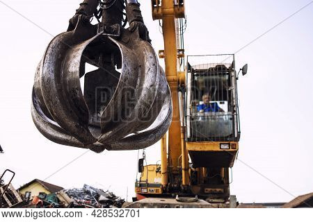 Man Operating Excavator Industrial Machine With Claw Attachment Used For Lifting Scrap Metal In Junk