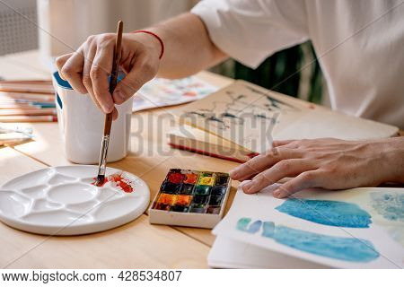 A Young Artist Paints With Watercolors In A Notebook Sitting At A Wooden Table. Beautiful Male Hands