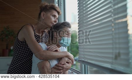 Lonely Senior Woman 90 Years Old In Medical Mask And Her Mature Daughter Standing In Embrace Looking